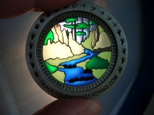 Sunburst Nature Walk Geocoin when held up to a light